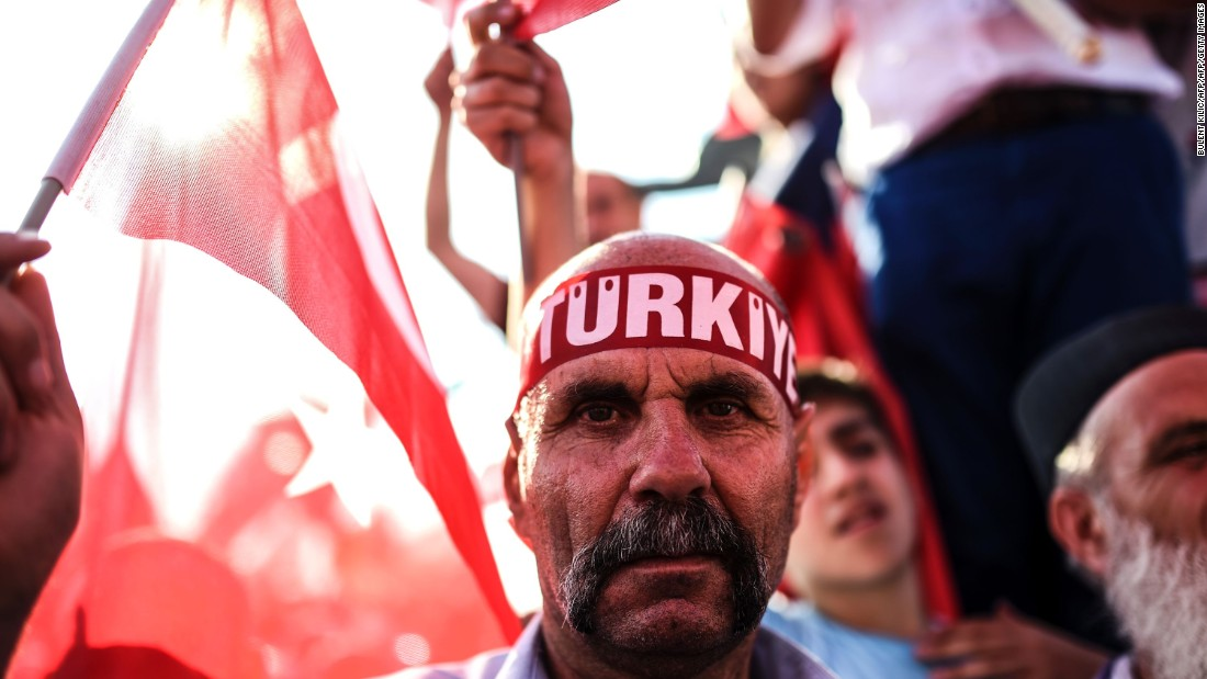 "A man wears a headband reading ""Turkey"" as thousands wave Turkish flags around him."