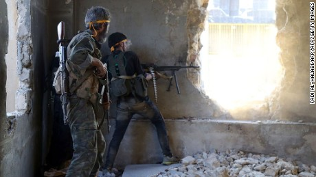 Rebel fighters fire at government positions in Ramouseh, southwest Aleppo Saturday.