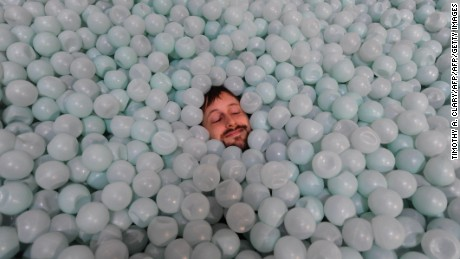 "Jesse Ragan lays in a ball pit at an art installation called ""Anthropodino"" by Brazilian artist Ernesto Neto on dispay at the Park Avenue Armory in New York May 15, 2009.The dramatic 55,000 square-foot, 80-foot-high piece will be on display until June 14, 2009. AFP PHOTO  TIMOTHY A. CLARY (Photo credit should read TIMOTHY A. CLARY/AFP/Getty Images)"