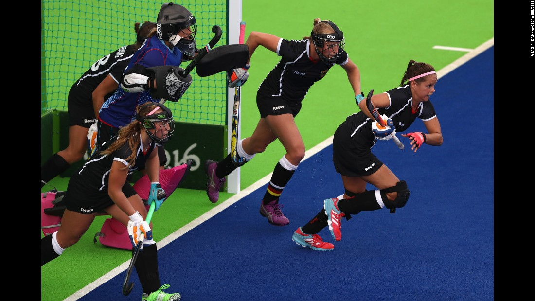 German field hockey players run from goal during a match against New Zealand.