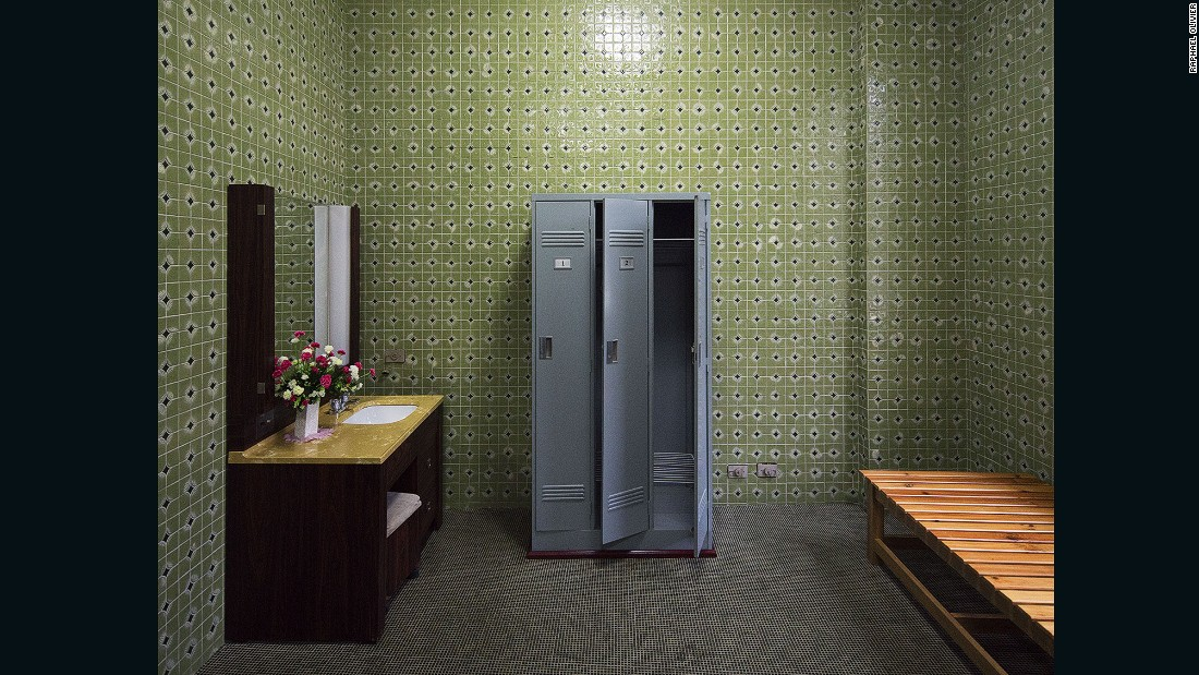 """Dressing room of a private sauna at the Changgwang-won health complex, featuring beautiful green tile work with black floor, matching the unique vintage tones of the city."""