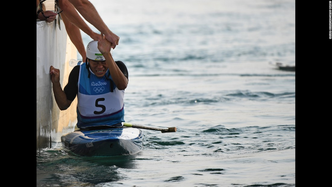 Japanese canoeist Takuya Haneda is congratulated after a ride in the C-1 slalom final. He won the bronze medal.