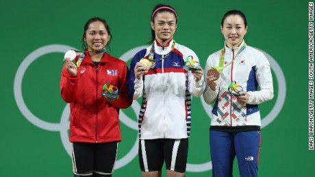 Hsu Shu-ching (middle) holds her gold medal alongside silver medalist Hidilyn Diaz of the Philippines and bronze medalist Jin Hee Yoon of South Korea.