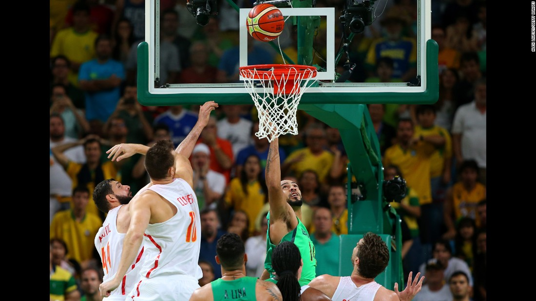 Brazilian basketball player Marcus Marquinhos, in green under the basket, tips in the winning basket to upset Spain 66-65.