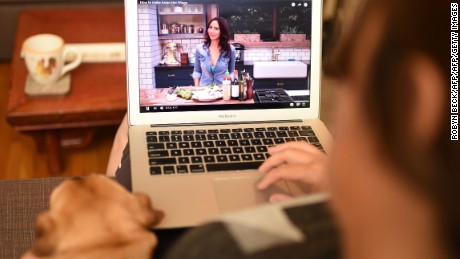 In this photo illustration, a woman and a dog watch a video by chef and YouTuber Caroline Artiss on her YouTube page, July 2, 2016 in Los Angeles, California. Self-described YouTuber Caroline Artiss has been a chef for 20 years, but opted out of restaurants and went to work for herself in catering in 2008. Then, a friend showed her how simple it was to make videos for YouTube. A media revolution is taking place, and most people over 35 years of age aren't tuned in. Millennials and their successors are shunning old-school television in favor of watching what they want whenever they wish on Google-owned YouTube or other video platforms like Dailymotion or Facebook.  / AFP / Robyn Beck        (Photo credit should read ROBYN BECK/AFP/Getty Images)