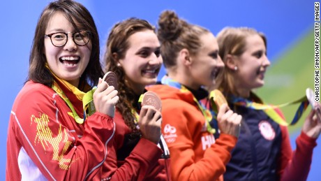 China's Fu Yuanhui on the medal podium. She charmed fans by eating a muffin during the live stream.