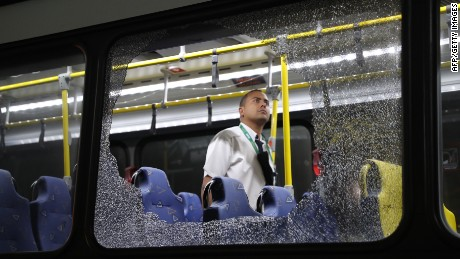 Two bus windows shattered after something struck the vehicle Tuesday as it transported journalists across Rio for the Olympics.