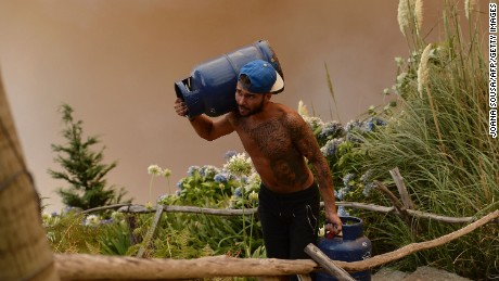 A man carries gas cylinders as a wildfire blazes in Funchal, Madeira.