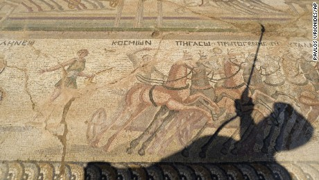 Fryni Hadjichristofi's shadow falls over the mosaic floor, depicting scenes from an ancient chariot race.