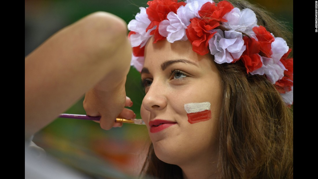 A Poland supporter has her face painted before a handball match.