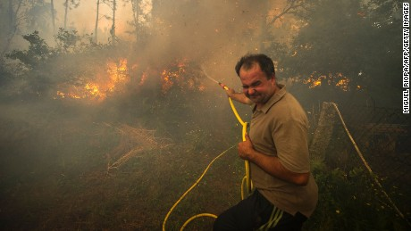 A man fights a wildfire with a garden hose in the Pontevedra region of northwestern Spain Thursday.