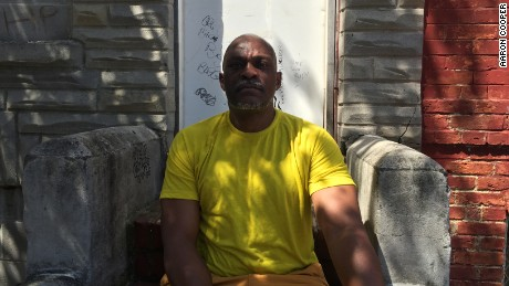 Rudolph Jackson, 52, sits on the stoop of a rowhouse near the spot where Freddie Gray was put into the back of a police van more than a year ago.