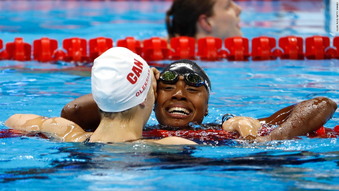 U.S. swimmer Simone Manuel, right, hugs Canadian Penny Oleksiak after they tied for first place in the 100-meter freestyle. They finished in an Olympic-record time of 52.70 seconds. Manuel is the first African-American woman to medal in an individual swimming event.