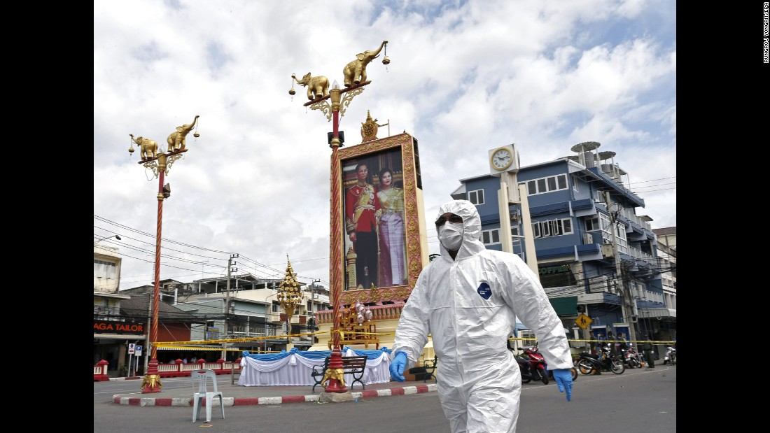 A Thai forensic police officer arrives to investigate the site of a blast after bombs exploded at the clock tower in the center of Hua Hin on August 12. The  attacks were carried out on a public holiday, celebrating Mother's Day and the birthday of Queen Sirikit, pictured here in a large portrait with Thai King Bhumibol Adulyadej.