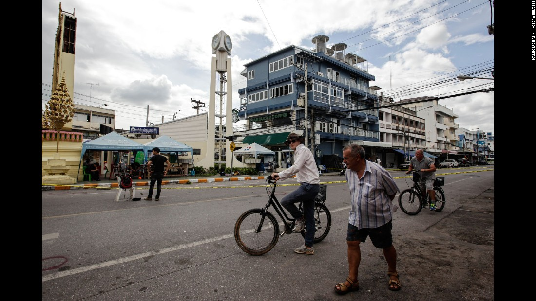 Tourists ride bicycles past the site of an explosion on Friday, August 12 in Hua Hin, Thailand.