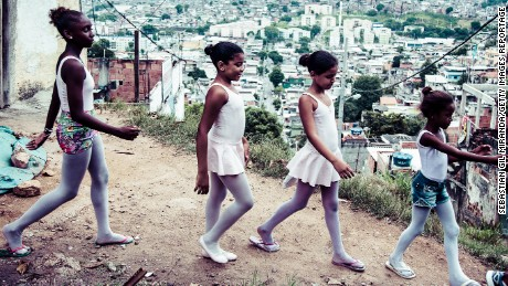 "RIO DE JANEIRO, BRAZIL - MARCH 21, 2015: Ballet students in the project ""Na Ponta dos Pés"" (On Tip of the Toes), organized by a former professional ballerina, Tuany Nascimento, in Complexo do Alemão, a favela in Rio de Janeiro. Students back home after the dance class, with view of the Complexo do Alemão.  (Photo by Sebastian Gil Miranda/Getty Images Reportage)"