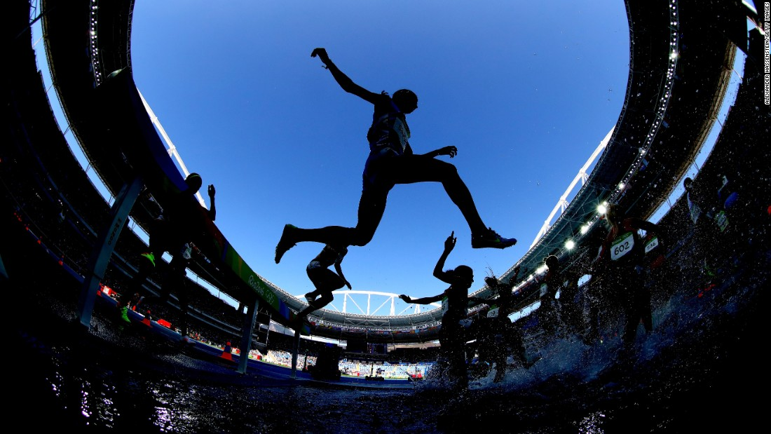 Athletes clear the water jump in the women's 3,000-meter steeplechase.