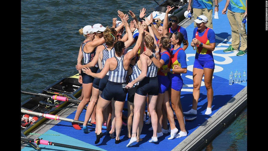 Team USA celebrates winning the gold with members of Romania's team, who won the bronze, in the women's eight rowing competition.