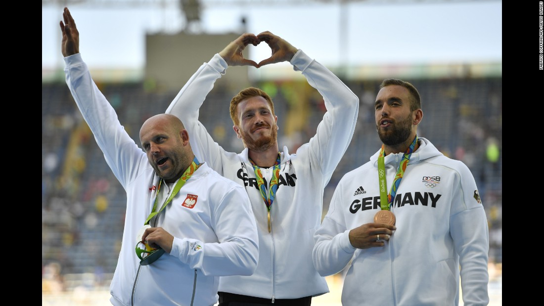Gold medalist Christoph Harting, center, and bronze medalist Daniel Jasinski, right, both of Germany, stand on the podium with silver medalist Piotr Malachowski of Poland to celebrate their discus throw wins.