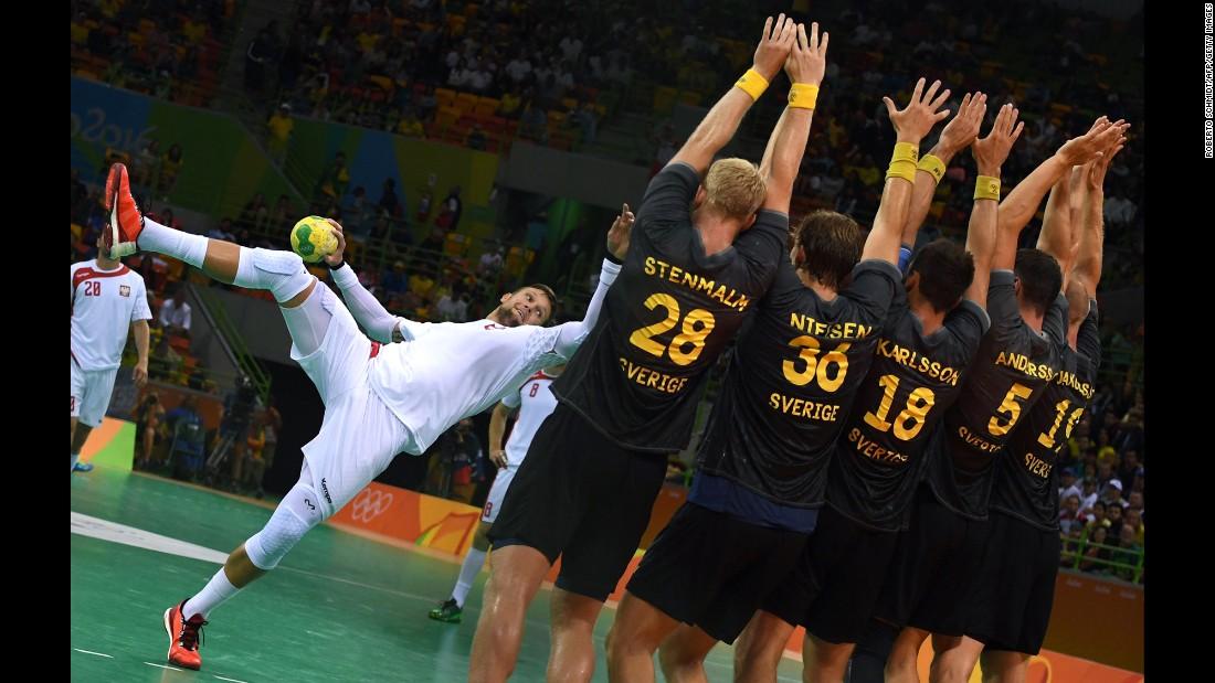 Polish handball player Kamil Syprzak takes a freethrow against Swedish defenders during their preliminary match.