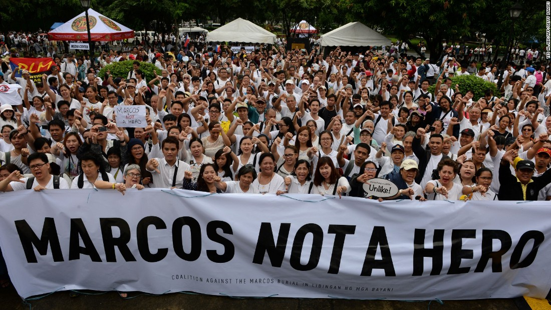 Protesters display placards with anti-Marcos slogans during a demonstration at a park in Manila on Sunday, August 14, 2016, against plans to honor the late dictator Ferdinand Marcos with a state burial.