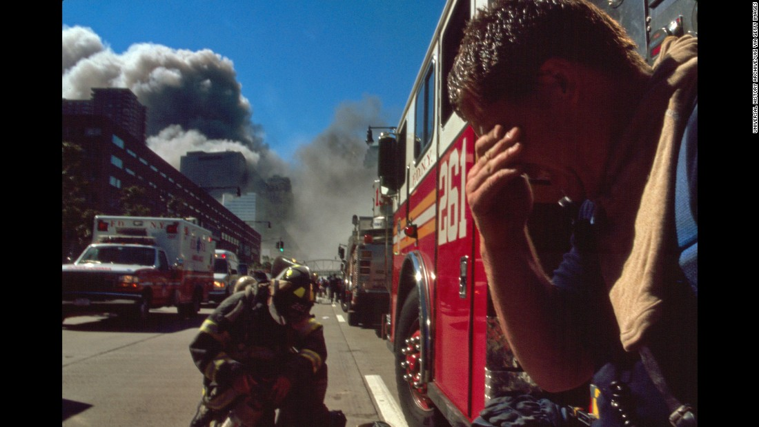A New York firefighter pauses as smoke rises in the background.