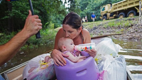 Danielle Blount kisses her 3-month-old baby Ember as she feeds her while they wait to be evacuated by members of the Louisiana Army National Guard near Walker, Louisiana, after heavy rains inundating the region, Sunday, Aug. 14, 2016.