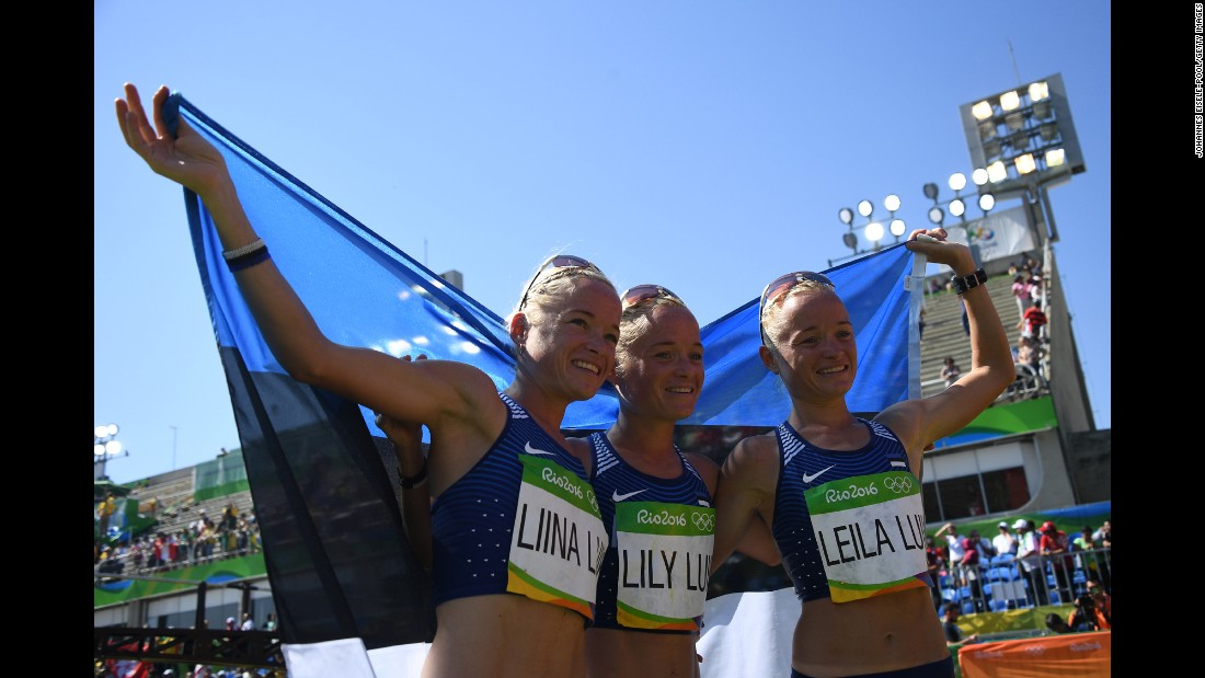 Triplets Liina Luik, Lily Luik and Leila Luik pose with the Estonian flag after taking part in the marathon on Sunday, August 14.