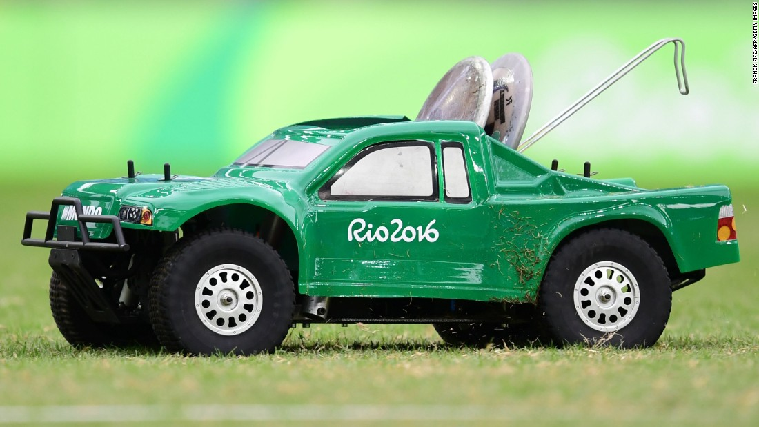 A remote-control car carries the discus during the men's qualifying round on Friday, August 12.