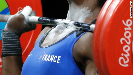 The barbell rests on the collarbones of Gaelle Verlaine Nayo Ketchanke, of France, as she performs a clean and jerk in the women's 75kg weightlifting competition at the 2016 Summer Olympics in Rio de Janeiro, Brazil, Friday, Aug. 12, 2016. (AP Photo/Mike Groll)