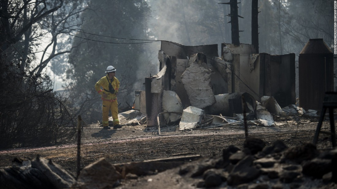 A firefighter from Palo Alto inspects damage from the Clayton fire near Main Street in Lower Lake.