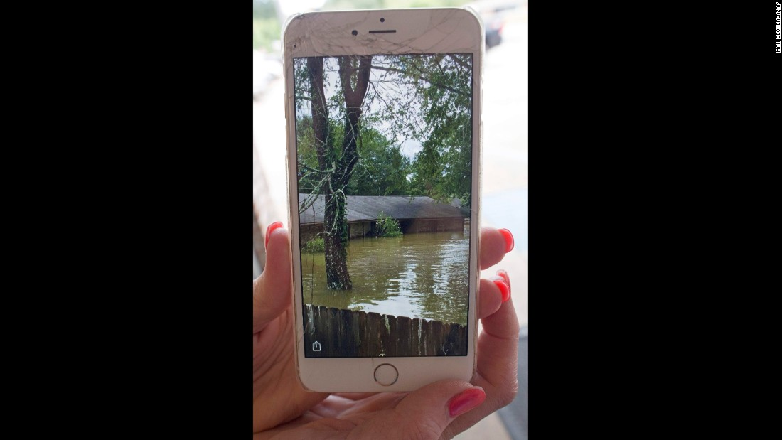 Noel Michael holds up a cell-phone photo of her flooded home in Livingston, Louisiana, on Monday, August 15.