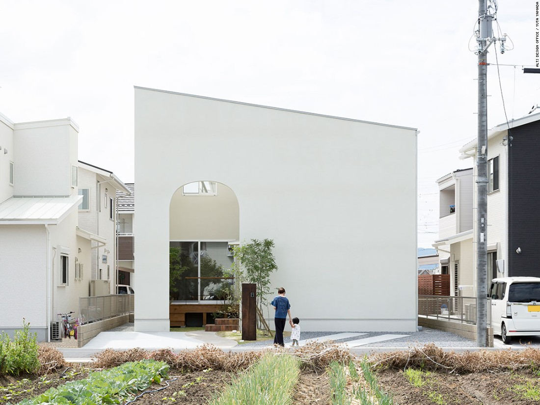 """Nicknamed the """"comfy house,"""" the 1,135-square-foot address from Alts Design Office brings together a welcoming atmosphere with various types of wood, natural light, vault-shaped doorways, and large curved windows."""