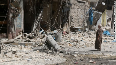 A resident of a rebel-held neighborhood in Aleppo inspects the damage from an airstrike Tuesday.