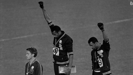"** FILE ** In this Oct. 16, 1968, file photo, United States athletes Tommie Smith, top center, and John Carlos, top right, extend their gloved fists skyward during the playing of the ""Star-Spangled Banner"" after Smith received the gold and Carlos the bronze for the 200-meter run at the Summer Olympic Games in Mexico City. Carlos and Smith raised their black-gloved fists on the medals stand as a symbol of protest 40 years ago at the Mexico City Olympics, creating an iconic image from the games. Australia's silver medalist Peter Norman is at left.  (AP Photo/file)"
