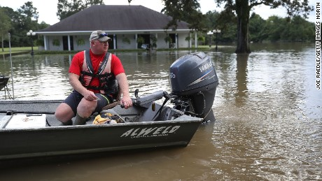 Richard Schafer navigates a boat past a flooded home on August 15, 2016 in Baton Rouge, Louisiana. Record-breaking rains pelted Louisiana over the weekend leaving the city with historic levels of flooding that have caused at least seven deaths and damaged thousands of homes.