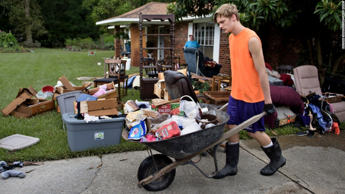 Kade Lewis helps gut his grandparents' home in Walker on Wednesday, August 17, after flooding.