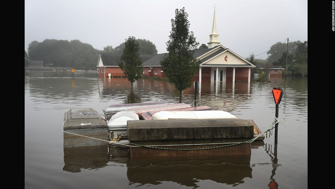Caskets float in floodwaters near a cemetery in Gonzales on August 17.