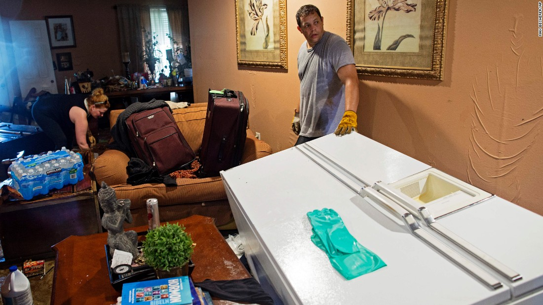 Raymond Lieteau waits for help to move a refrigerator as his friend Melissa Lockhart helps clean up the living room in his flood-damaged home in Baton Rouge on August 16. Lieteau had more than 5 feet of water in his home.