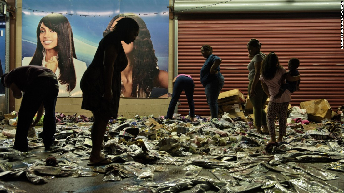 People sort through water-damaged products outside Jasmine's Beauty Supply in Baton Rouge on August 16.