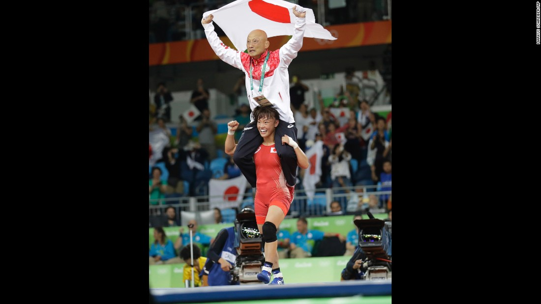 Another Japanese wrestler, Eri Tosaka, carries her coach on her shoulders after winning gold in her weight class.