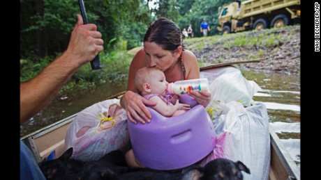 Danielle Blount kisses her 3-month-old baby Ember as she feeds her while they wait to be evacuated by members of the Louisiana Army National Guard near Walker, La., after heavy rains inundating the region, Sunday, Aug. 14, 2016. (AP Photo/Max Becherer)
