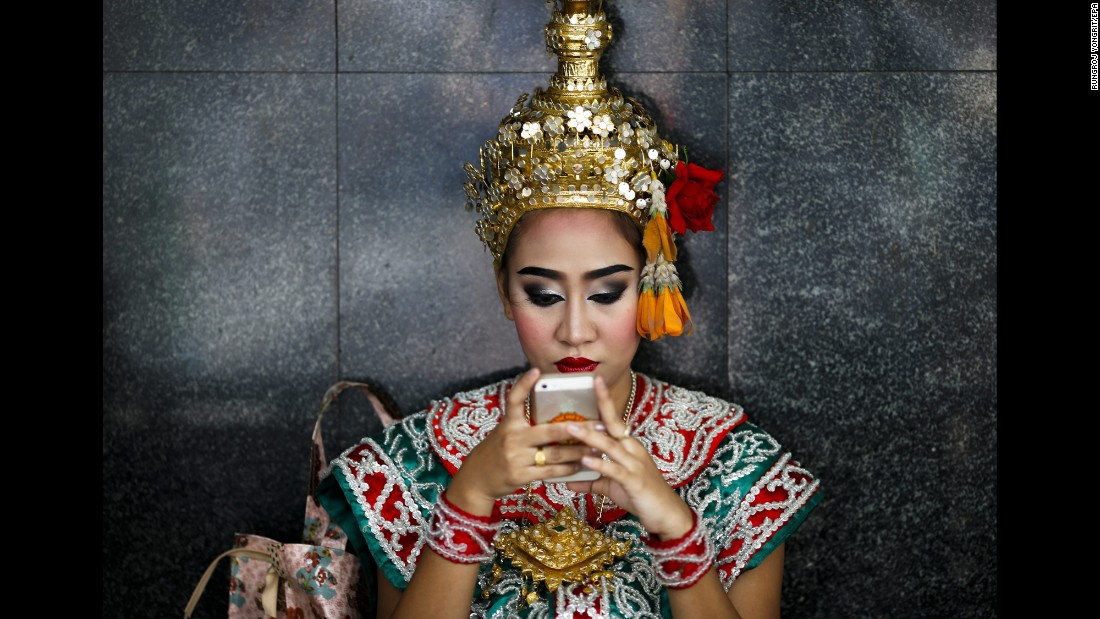 "A dancer uses her cell phone at the Erawan Shrine in Bangkok, Thailand, on Tuesday, August 16. The Hindu shrine was the target of <a href=""http://www.cnn.com/2015/08/17/travel/thailand-shrine/"" target=""_blank"">a bombing that killed at least 20 people</a> in August 2015."