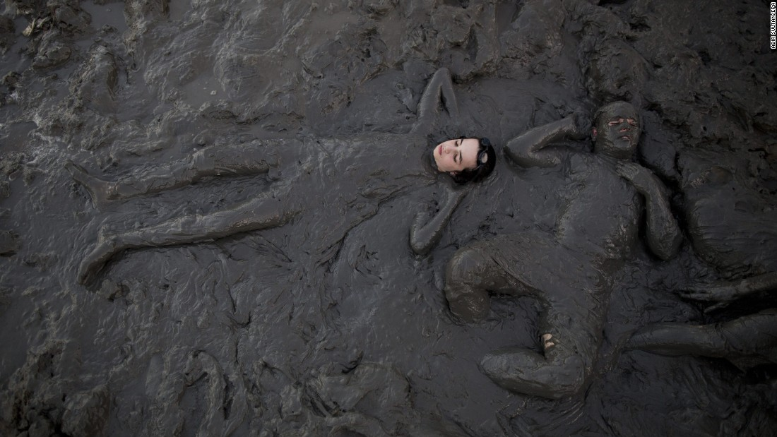 People smear themselves with mud at a Dead Sea beach in Israel on Tuesday, August 16.