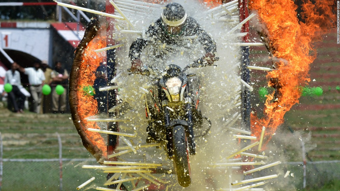 A police officer rides a motorcycle through a flaming hoop and a wall of glass tubes during an Independence Day event in Srinagar, India, on Monday, August 15.