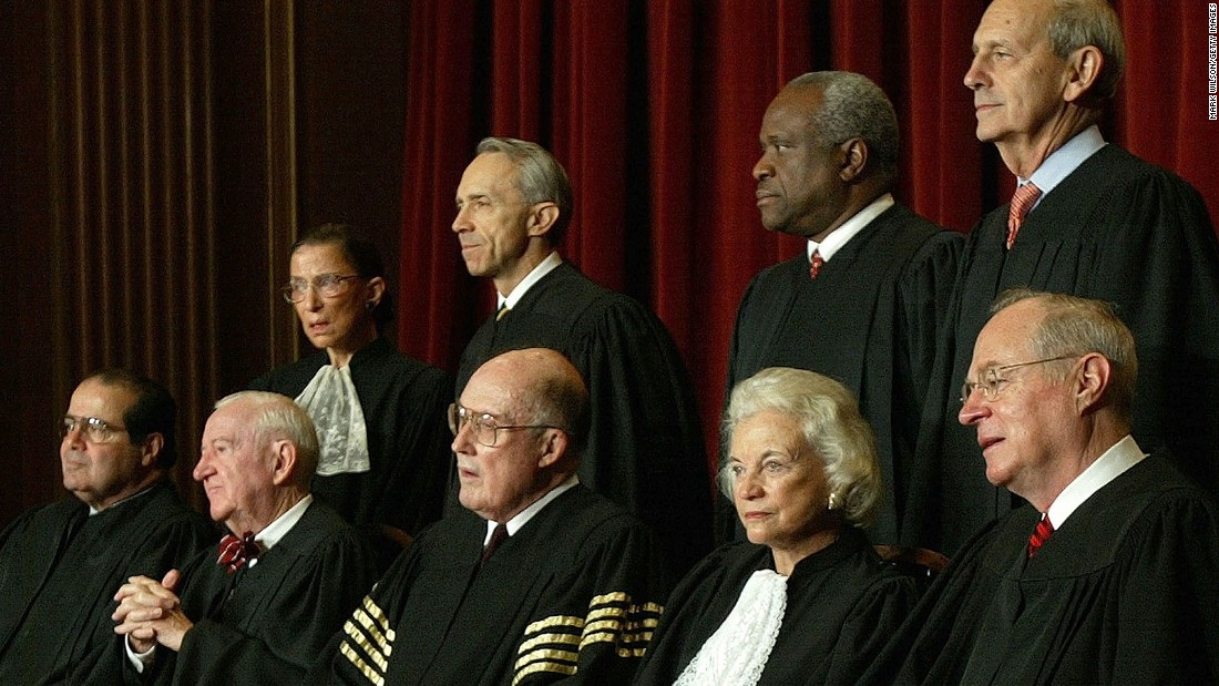 O'Connor takes a photo with the rest of the Supreme Court justices in December 2003. Seated, from left, are Antonin Scalia, John Paul Stevens, Chief Justice William Rehnquist, O'Connor and Anthony Kennedy. Standing, from left, are Ruth Bader Ginsburg, David Souter, Clarence Thomas and Stephen Breyer.