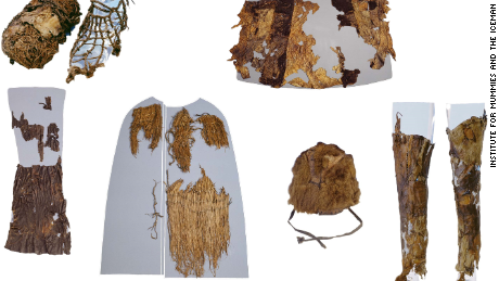 Otiz's clothing are on display from top left: A shoe with grass interior (left) and leather exterior (right), the leather coat (reassembled by the museum), leather loincloth, grass coat, fur hat, and leather leggings.