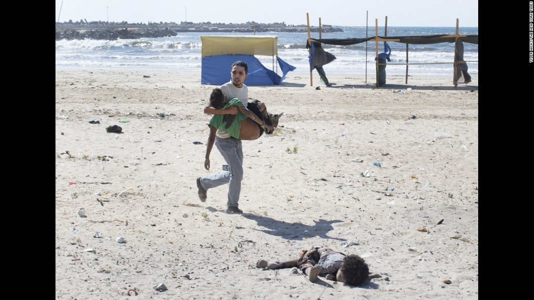 "<strong>2014: Gaza City </strong>-- A man carries a child as another lies dead after an Israeli airstrike on a Gaza City beach in July 2014. At least four boys, ages 9 to 11, were killed. The Israeli military investigated the tragedy and reported that the location of the attack was known to be a compound of Hamas police and naval forces. ""Tragically, in the wake of the incident it became clear that the outcome of the attack was the death of four children who had entered the military compound for reasons that remain unclear,"" <a href=""http://www.cnn.com/2015/06/11/middleeast/israel-gaza-beach-bombing/"" target=""_blank"">the report stated.</a>"