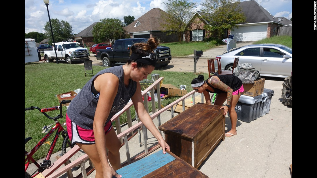 "Owens' roommate, Staff Sgt. Pamela Vance, right, and her sister, Jennifer, carry some of Vance's and Owens' prized furniture pieces out of their home. Vance hails from Slidell, Louisiana, and was a victim of Hurricane Katrina. She likens the flooding in Denham Springs to the devastating 2005 natural disaster. ""All these emotions run through, and you say: 'God, why? Again? Everything you worked for?' """