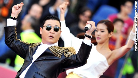 Korean pop artist Park Jae Sang, popularly known as 'Psy', sings as he performs his 'Gangnam Style' song prior to the Italian Cup football final between AS Roma and Lazio at the Rome's Olympic stadium on May 26, 2013. AFP PHOTO / TIZIANA FABI        (Photo credit should read TIZIANA FABI/AFP/Getty Images)